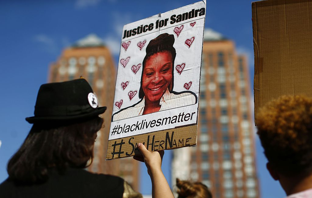A woman holds a poster bearing the portrait of  Sandra Bland, a 28-year-old black woman who killed herself in a Texas jail cell on July 13th,   during a Michael Brown memorial rally on Union Square August 9, 2015 in New York.  Demonstrators showed support on the one year anniversary  on the death of 18-year-old Michael Brown, an unarmed black teen who was shot and killed in Ferguson, Missouri by a white police officer, Darren Wilson, throwing America's troubled race relations into harsh relief.     AFP PHOTO / KENA BETANCUR
