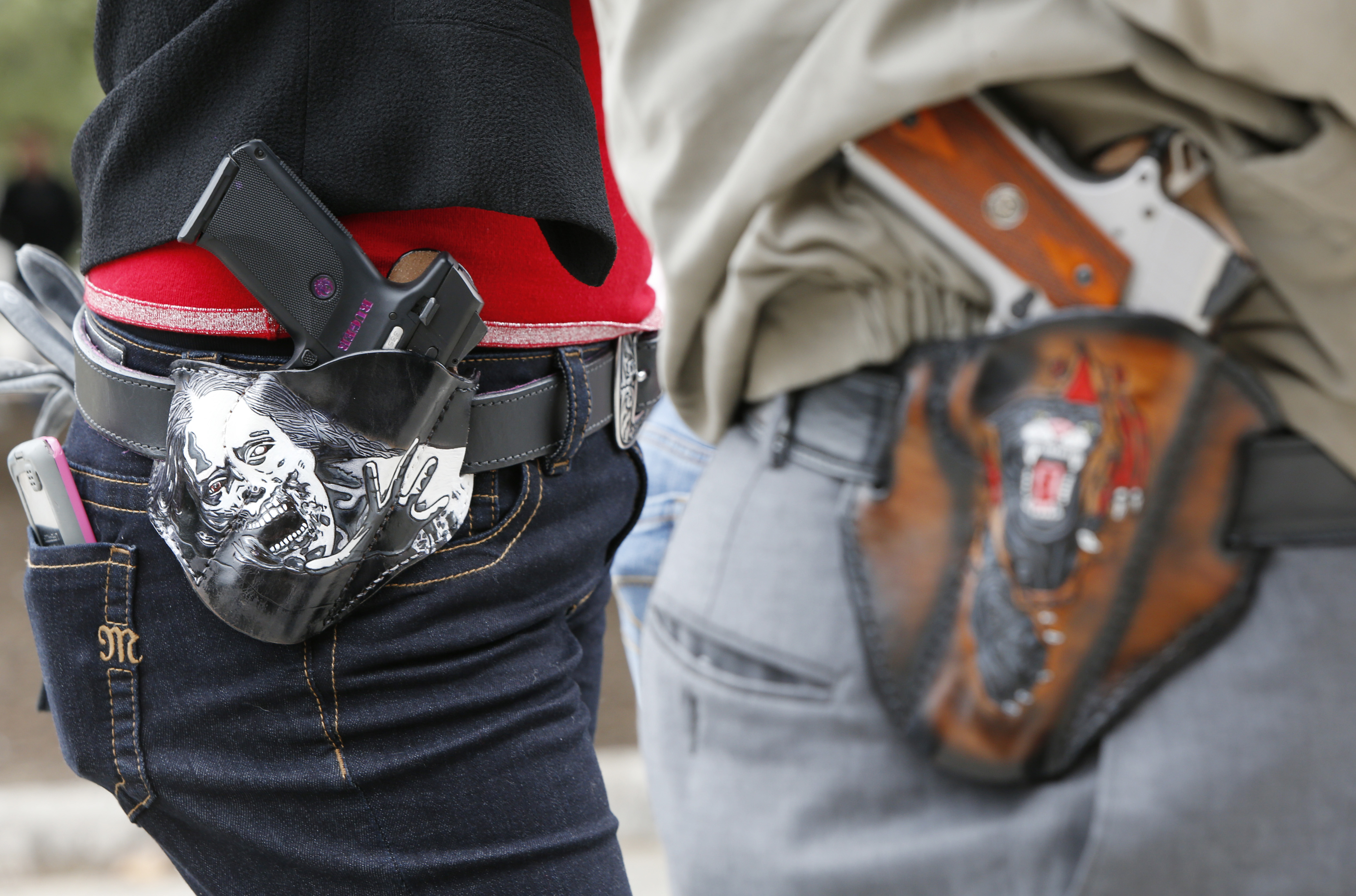 AUSTIN, TX - JANUARY 1: Art and Diana Ramirez of Austin with their pistols in custom-made holsters during and open carry rally at the Texas State Capitol on January 1, 2016 in Austin, Texas. On January 1, 2016, the open carry law takes effect in Texas, and 2nd Amendment activists hold an open carry rally.